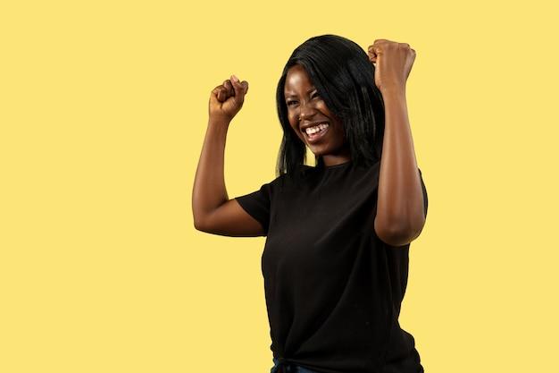 Jeune femme afro-américaine isolée sur fond de studio jaune, expression faciale. beau portrait de femme demi-longueur. concept d'émotions humaines, expression faciale. fou heureux, en train de célébrer.