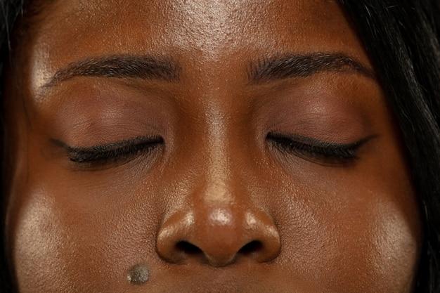 Jeune femme afro-américaine isolée sur fond de studio jaune, expression faciale. les yeux de la belle femme bouchent le portrait. concept d'émotions humaines, expression faciale.