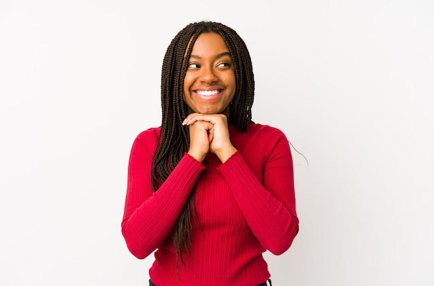 Jeune femme afro-américaine isolée garde les mains sous le menton, regarde joyeusement de côté.