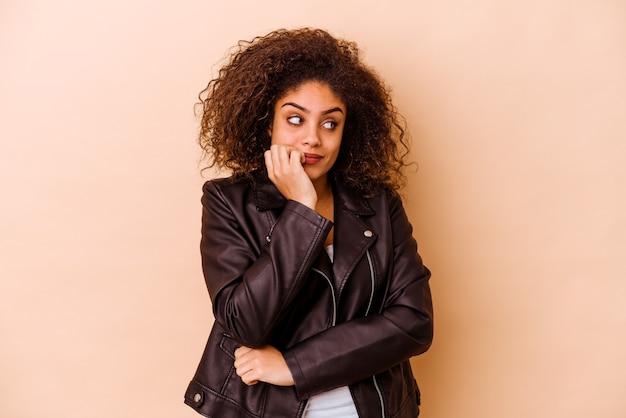 Jeune femme afro-américaine isolée sur un mur beige se mordant les ongles, nerveuse et très anxieuse.