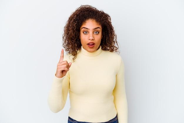 Jeune femme afro-américaine isolée sur un mur blanc ayant une idée