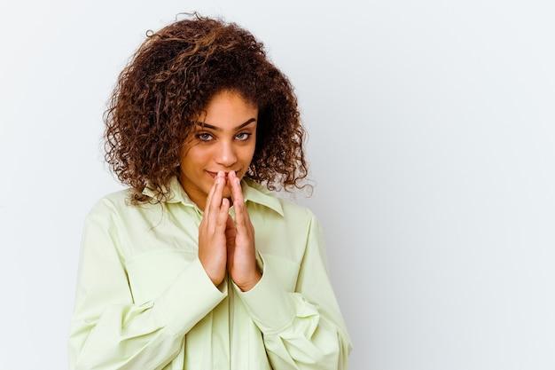 Jeune femme afro-américaine isolée sur un mur blanc constituant un plan à l'esprit, la mise en place d'une idée