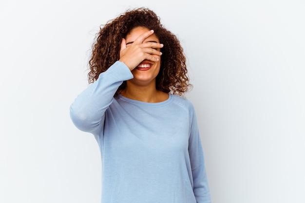 Jeune femme afro-américaine isolée sur un mur blanc couvre les yeux avec les mains, sourit largement en attente d'une surprise