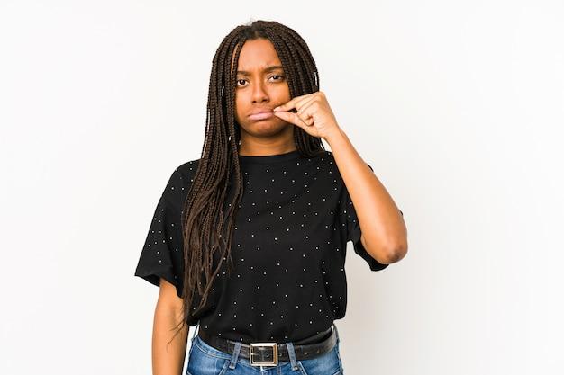 Jeune femme afro-américaine isolée sur mur blanc avec les doigts sur les lèvres gardant un secret.