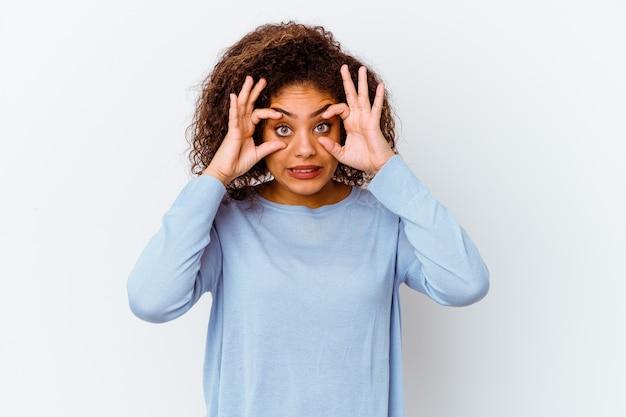 Jeune femme afro-américaine isolée sur un mur blanc en gardant les yeux ouverts pour trouver une opportunité de succès