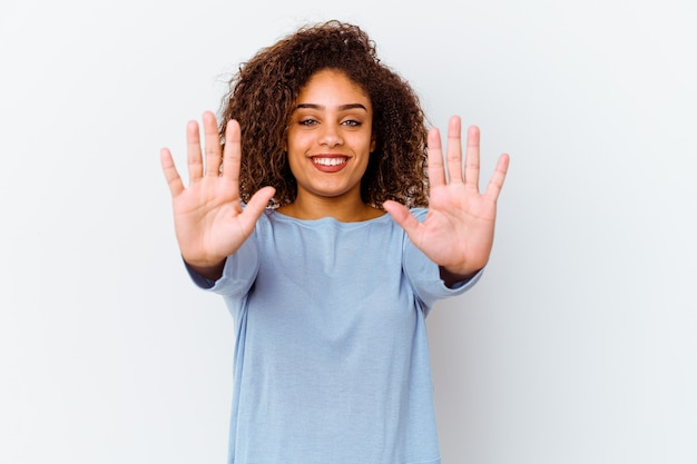 Jeune femme afro-américaine isolée sur un mur blanc montrant le numéro dix avec les mains