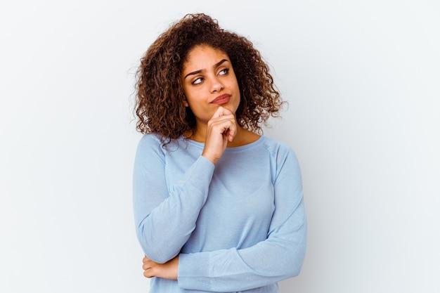 Jeune femme afro-américaine isolée sur un mur blanc pensant et levant, réfléchissant, contemplant, ayant un fantasme