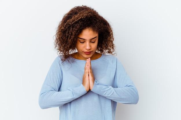 Jeune femme afro-américaine isolée sur un mur blanc priant, montrant la dévotion, personne religieuse à la recherche d'inspiration divine.