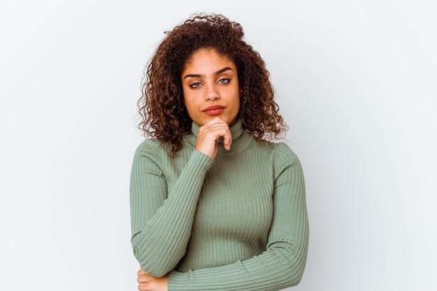 Jeune femme afro-américaine isolée sur un mur blanc suspect, incertain, vous examinant