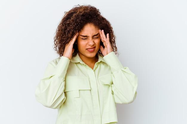 Jeune femme afro-américaine isolée sur un mur blanc touchant les tempes et ayant mal à la tête.