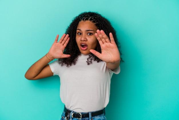 Jeune femme afro-américaine isolée sur un mur bleu choqué en raison d'un danger imminent