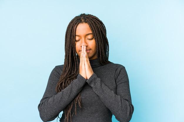 Jeune femme afro-américaine isolée sur le mur bleu, main dans la main en priant près de la bouche, se sent en confiance.