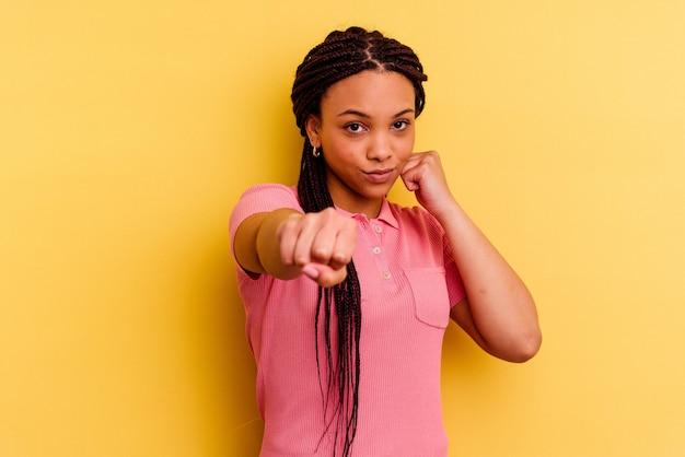 Jeune femme afro-américaine isolée sur mur jaune jetant un coup de poing, la colère, les combats en raison d'une dispute, la boxe