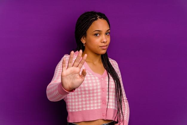 Jeune femme afro-américaine isolée sur mur jaune jeune femme afro-américaine isolée sur mur jaune étant choquée en raison d'un danger imminent