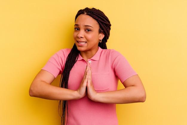 Jeune femme afro-américaine isolée sur un mur jaune avec les mains en priant près de la bouche, se sent en confiance.