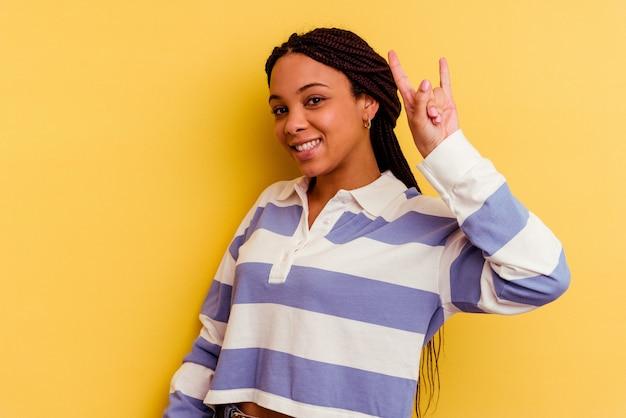 Jeune femme afro-américaine isolée sur un mur jaune montrant un geste de cornes comme un concept de révolution.