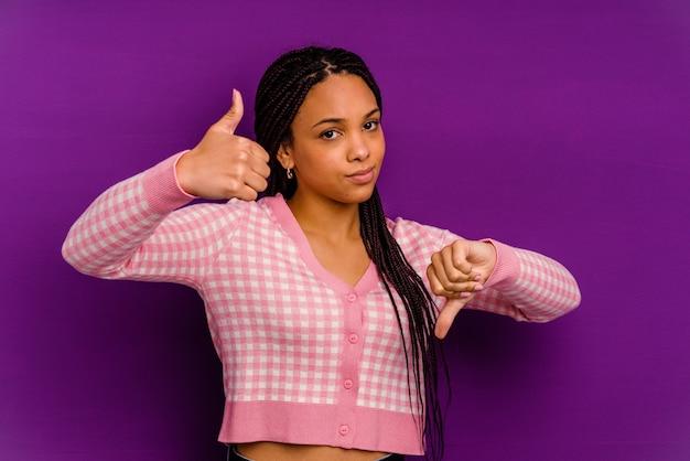 Jeune femme afro-américaine isolée sur un mur jaune montrant les pouces vers le haut et les pouces vers le bas