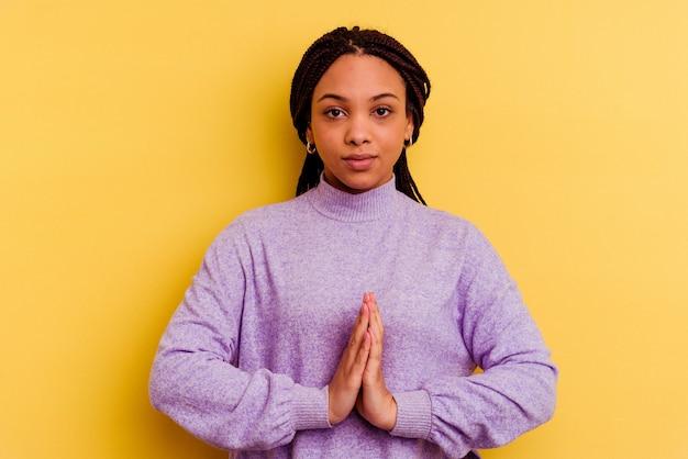 Jeune femme afro-américaine isolée sur mur jaune priant, montrant la dévotion, personne religieuse à la recherche d'inspiration divine