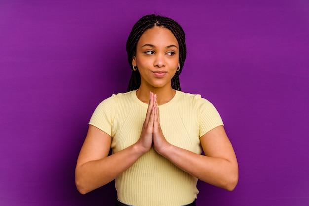 Jeune femme afro-américaine isolée sur le mur jaune priant, montrant la dévotion, personne religieuse à la recherche d'inspiration divine.