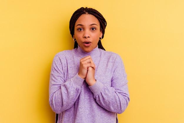 Jeune femme afro-américaine isolée sur un mur jaune priant pour la chance, étonné et ouvrant la bouche à l'avant