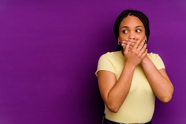 Jeune femme afro-américaine isolée sur un mur jaune réfléchie à la recherche d'un espace de copie couvrant la bouche avec la main.