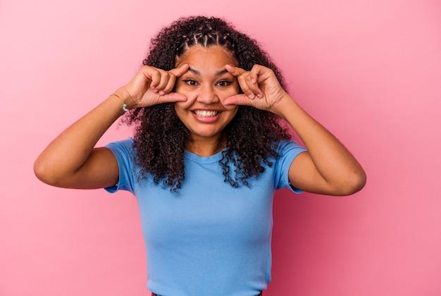 Jeune femme afro-américaine isolée sur un mur rose en gardant les yeux ouverts pour trouver une opportunité de succès.