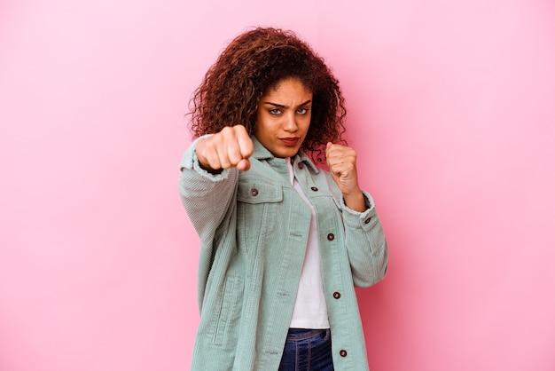 Jeune femme afro-américaine isolée sur un mur rose, jetant un coup de poing, la colère, les combats en raison d'une dispute, la boxe.