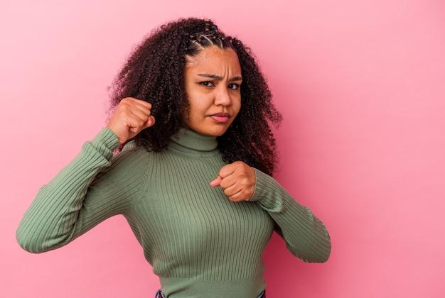 Jeune femme afro-américaine isolée sur un mur rose en jetant un coup de poing, la colère, les combats en raison d'une dispute, la boxe
