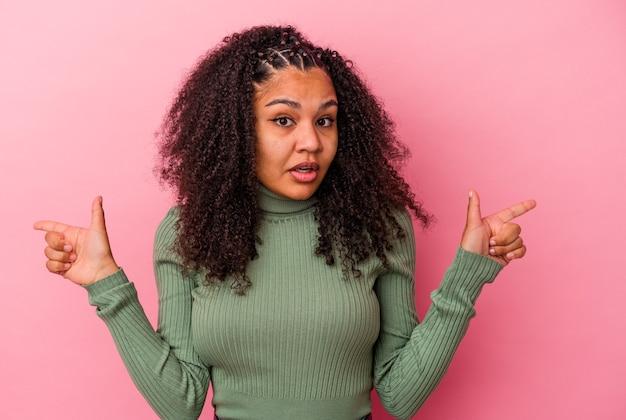 Jeune femme afro-américaine isolée sur un mur rose pointant vers différents espaces de copie, en choisissant l'un d'entre eux, montrant avec le doigt