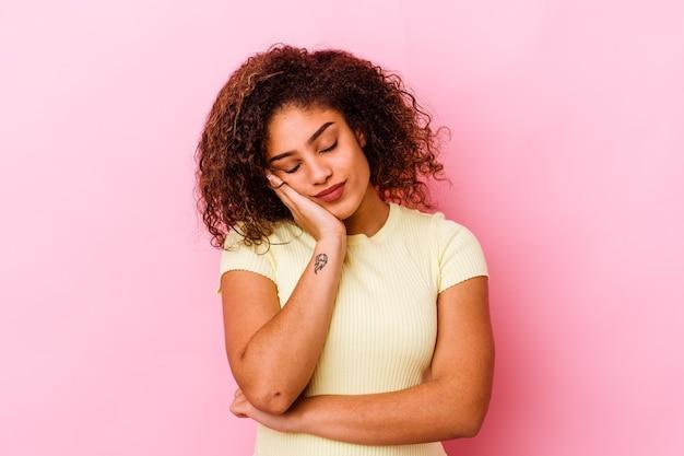 Jeune femme afro-américaine isolée sur un mur rose qui s'ennuie, fatigué et a besoin d'une journée de détente