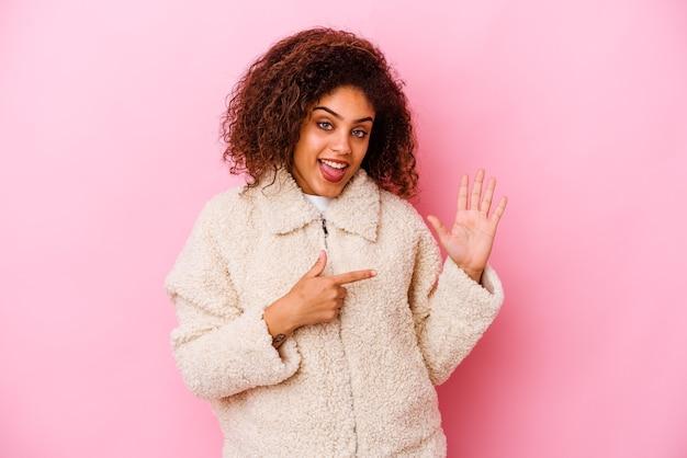 Jeune femme afro-américaine isolée sur mur rose souriant joyeux montrant le numéro cinq avec les doigts