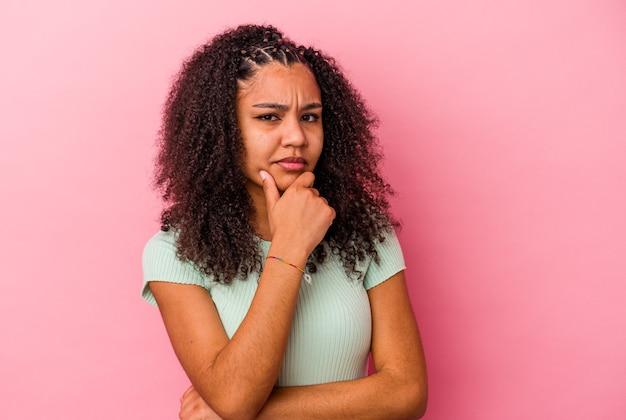 Jeune femme afro-américaine isolée sur un mur rose suspect, incertain, vous examine.