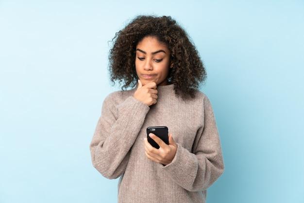Jeune femme afro-américaine isolée sur la pensée bleue et l'envoi d'un message