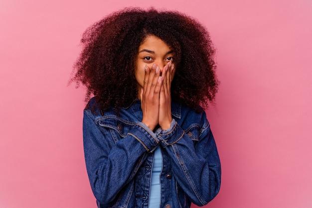 Jeune femme afro-américaine isolée sur rose choquée, couvrant la bouche avec les mains, impatiente de découvrir quelque chose de nouveau.