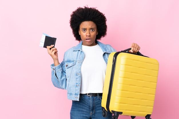 Jeune femme afro-américaine isolée sur rose malheureux en vacances avec valise et passeport