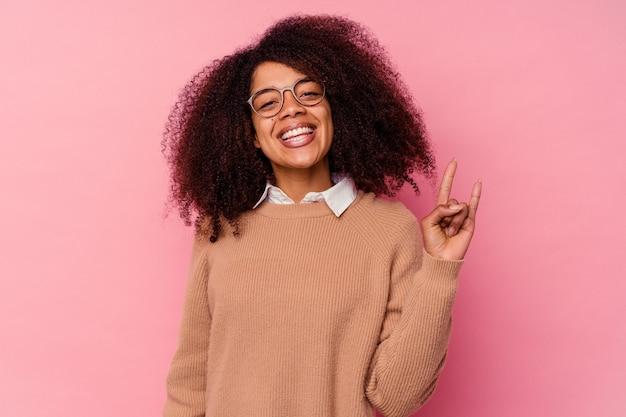 Jeune femme afro-américaine isolée sur rose montrant un geste de cornes comme concept de révolution.