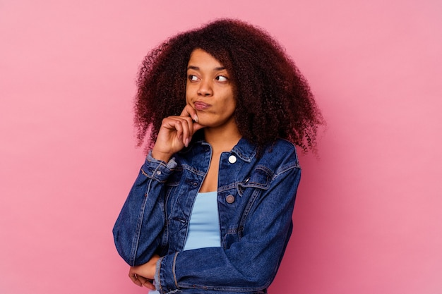 Jeune femme afro-américaine isolée sur rose pensant et levant, réfléchissant, contemplant, ayant un fantasme.