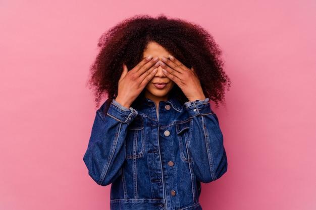 Jeune femme afro-américaine isolée sur rose peur couvrant les yeux avec les mains.