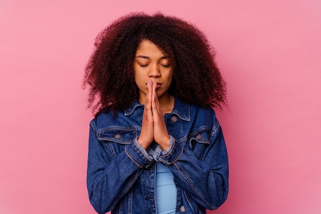 Jeune femme afro-américaine isolée sur rose priant, montrant la dévotion, personne religieuse à la recherche d'inspiration divine.