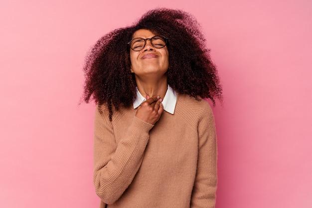 Une jeune femme afro-américaine isolée sur rose souffre de douleurs dans la gorge à cause d'un virus ou d'une infection.