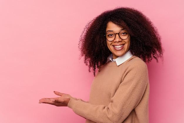 Jeune femme afro-américaine isolée sur rose tenant un espace de copie sur une paume.