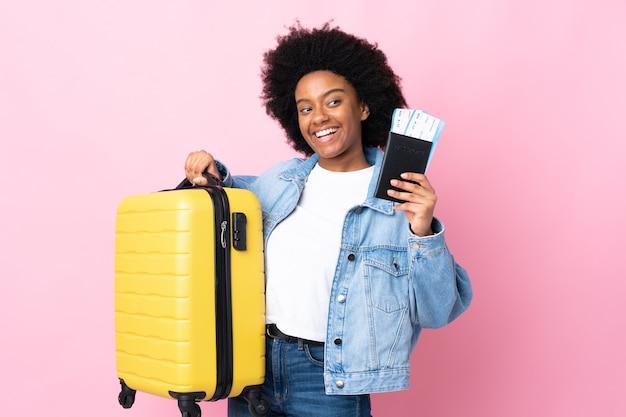 Jeune femme afro-américaine isolée sur rose en vacances avec valise et passeport