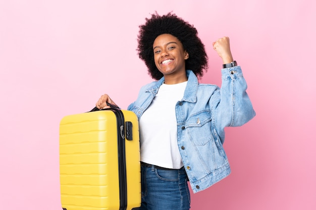Jeune femme afro-américaine isolée sur rose en vacances avec valise de voyage