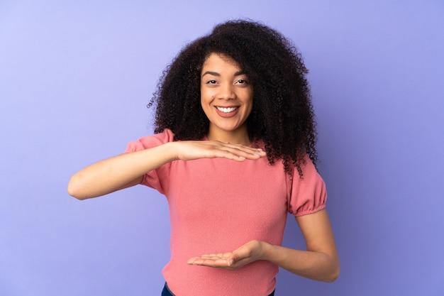 Jeune femme afro-américaine isolée tenant copyspace imaginaire