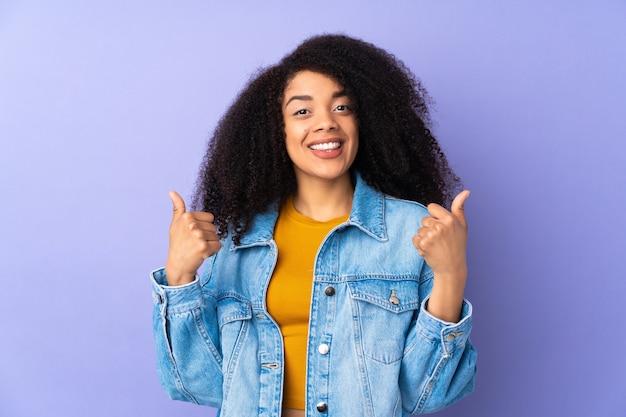 Jeune femme afro-américaine isolée sur violet donnant un geste de pouce en l'air