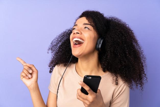Jeune femme afro-américaine isolée sur violet écoute de la musique avec un mobile et le chant