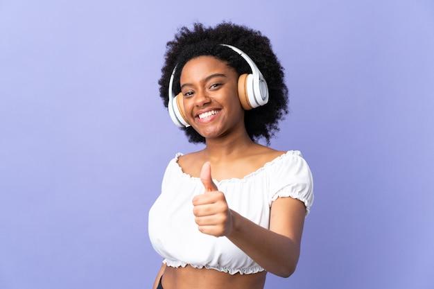 Jeune femme afro-américaine isolée sur violet écoute de la musique et avec le pouce vers le haut