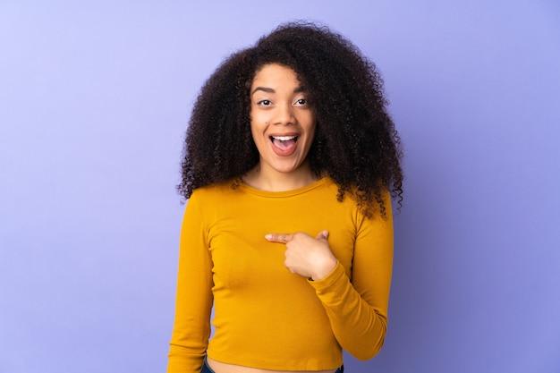 Jeune femme afro-américaine isolée sur violet avec expression faciale surprise