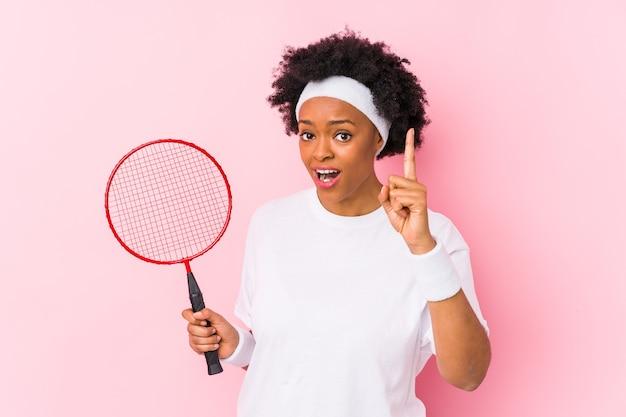 Jeune femme afro-américaine jouant au badminton isolée ayant une idée, concept d'inspiration.