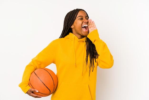 Jeune femme afro-américaine jouant au basket-ball isolé criant et tenant la paume près de la bouche ouverte.